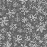 Seamless pattern of many layers of snowflakes. Christmas seamless pattern of many layers of snowflakes of different shapes, sizes and transparency. White on gray Royalty Free Stock Photo