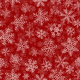 Seamless pattern of many layers of snowflakes. Christmas seamless pattern of many layers of snowflakes of different shapes, sizes and transparency. White on red Royalty Free Stock Image