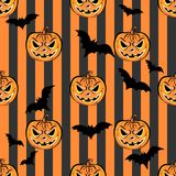 Seamless pattern with orange halloween pumpkins and bats. On striped background. Halloween design template for scrap-book paper, textile print, page fill Stock Image