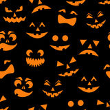 Seamless pattern with orange halloween pumpkins carved faces silhouettes on black background. Vector illustration Stock Image