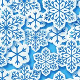 Seamless pattern with paper snowflakes. On blue Royalty Free Stock Photo