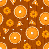 Seamless pattern with pumpkin pies and pumpkins on a wooden background. Vector illustration. Vector seamless pattern with pumpkin pies, pumpkins and seeds on a Royalty Free Stock Photo