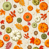 Seamless pattern with pumpkins and autumn leaves on a wooden background. Vector illustration. Royalty Free Stock Photography