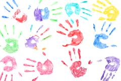 Seamless pattern with rainbow colored kids hand prints on white background stock photos