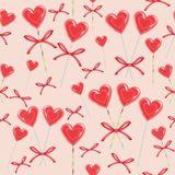 Seamless pattern. Red candy in the shape of heart bandaged with ribbon. Valentine`s gift for St. Valentine`s Day. Vector stock illustration