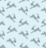 Seamless pattern with running hare. Seamless pattern with gray running hare on the blue background Royalty Free Stock Images