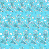 Seamless pattern of sweet ice cream in a waffle cone surrounded by flowers and circles on a light blue background. Stock Photos