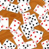 Seamless pattern texture background playing cards irregularly scattered on the woody table Royalty Free Stock Images