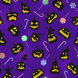 Seamless illustration  on the theme of Halloween, pumpkins with faces and sweets on a dark purple background Royalty Free Stock Photography