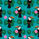 Seamless pattern with toucan bird sitting on branch around palm monstera leaves and flowers. Nature colorful jungle seamless pattern with toucan bird sitting on Stock Photo