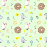 Seamless pattern with watercolor Easter rabbits, bird nests, eggs, birds, yellow and green branches. Hand drawn isolated on a light green background Royalty Free Stock Photo
