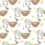 Seamless pattern with watercolor Easter rabbits, nests with bird eggs, yellow and green branches. Hand drawn isolated on a white background Stock Photography
