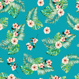 Seamless pattern with watercolor palm and monstera leaves, exotic pink flowers. Hand painted on a dark turquoise background Royalty Free Stock Images