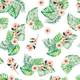 Seamless pattern with watercolor palm and monstera leaves, exotic pink flowers. Hand painted on a white background Stock Image