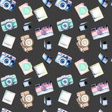 Seamless pattern with watercolor retro cameras, snapshots and films. Hand drawn isolated on a dark background Stock Images