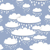 Seamless pattern with white clouds and raindrops on a blue background Royalty Free Stock Images