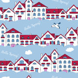 Seamless pattern of white houses and clouds. Royalty Free Stock Photo