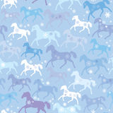 Seamless pattern with wild horses and snowflakes o. N winter light blue background Royalty Free Stock Image