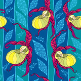 Seamless pattern with yellow Cypripedium calceolus or Lady's slipper orchid and ornate leaves on the blue background. Royalty Free Stock Photos