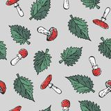 Seamless poisonous blody-red amanita mushrooms and green stinging nettle leaves pattern texture element on grey background.  Royalty Free Stock Image