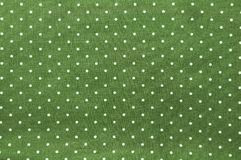 Seamless polka dots pattern on green fabric. Background stock images