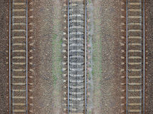 Seamless railroad Pattern, backdrop. With space for text. Top view. Shiny iron rails and concrete sleepers, coupled with powerful bolts on stony ground Royalty Free Stock Image