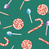 A seamless sweet pattern with the watercolor lollipop and candy cane. Painted hand-drawn on a green background Stock Image