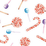 A seamless sweet pattern with the watercolor lollipop and candy cane. Painted hand-drawn on a white background. A seamless sweet pattern with the lollipop and Stock Images