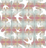 Seamless texture with the swallows, and triangles. Mosaic effect or kaleidoscope  Pastel spring colors  Silhouettes of birds Royalty Free Stock Images
