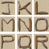 Seamless Tiling Driftwood Alphabet J - R. Alphabet J - R made from photos of driftwood on background photo of sand. Will tile seamlessly horizontally or Stock Photo
