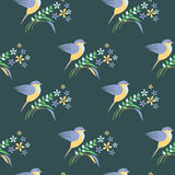 Seamless vector pattern with animals. Symmetrical background with colorful birds, leaves and flowers on the blue backdrop Royalty Free Stock Photos