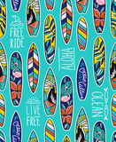 Seamless vector pattern with bright surfboards and stylish phrases on the blue background. Royalty Free Stock Photos