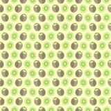 Seamless vector pattern, mat symmetrical background with elements of kiwi, whole and cut, over light yellow background Stock Photo