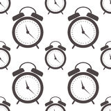 Seamless vector pattern. Symmetrical background with closeup black alarm clocks on the white background.  Stock Photo