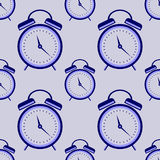 Seamless vector pattern. Symmetrical background with closeup blue alarm clocks on the blue background Stock Photo