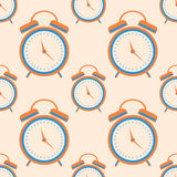 Seamless vector pattern. Symmetrical background with orange closeup alarm clocks on the light background.  Stock Photo