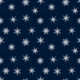 Seamless winter pattern of Lacy snowflakes on blue background Stock Images