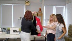Seamster教她的学生缝合衣裳显示在夹克的细节在路线 股票视频