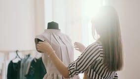 Seamstress ο σχεδιαστής διορθώνει τις πτυχές για το φόρεμα των εύκολων γυναικών απόθεμα βίντεο