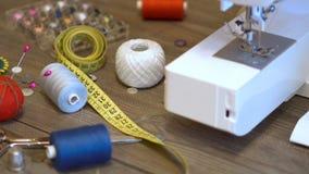 Seamstress ή ραφτών εργασιακός χώρος με το ράψιμο των εργαλείων, των νημάτων και της ράβοντας μηχανής φιλμ μικρού μήκους