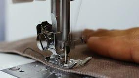 Seamstress ατόμων το ύφασμα εκμετάλλευσης χεριών πίσω από τη ράβοντας μηχανή ράβει το ύφασμα απόθεμα βίντεο
