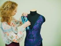 Seamstress γυναικών που εργάζεται στο στούντιό του Το μανεκέν φορά ένα κομπινεζόν δαντελλών στοκ εικόνες