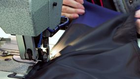 Seamstress εργασιακών χώρων στο εργοστάσιο ενδυμάτων Μια σύγχρονη ράβοντας μηχανή σε λειτουργία Ράψιμο μιας επένδυσης για ένα σακ φιλμ μικρού μήκους