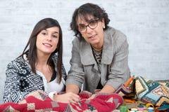 Seamstress και ο μαθητευόμενός της με το ύφασμα για την προσθήκη Στοκ εικόνες με δικαίωμα ελεύθερης χρήσης