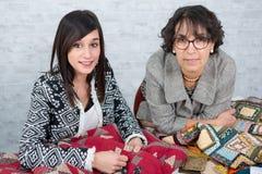 Seamstress και ο μαθητευόμενός της με το ύφασμα για την προσθήκη Στοκ εικόνα με δικαίωμα ελεύθερης χρήσης