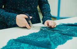 Seamstress κοριτσιών που εργάζεται στο στούντιό του Θηλυκά χέρια που κρατούν ένα ψαλίδι στοκ φωτογραφία