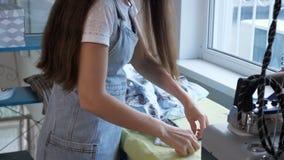 Seamstress λεπτομέρειες σιδερώματος των ενδυμάτων στο ράψιμο του εργαστηρίου της προσαρμογής της επιχείρησης απόθεμα βίντεο