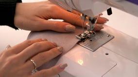 Seamstress πίσω από τη ράβοντας μηχανή, τις εργασίες μηχανών, το θηλυκή ράφτη ή τη μοδίστρα στην εργασία, ράβοντας μηχανή, ύφασμα απόθεμα βίντεο