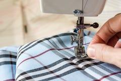 Seamstress περνά κλωστή σε μια βελόνα και προετοιμάζεται για το ράψιμο με τη μηχανή στοκ εικόνα