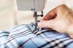 Seamstress περνά κλωστή σε μια βελόνα και προετοιμάζεται για το ράψιμο με τη μηχανή Στοκ Φωτογραφίες